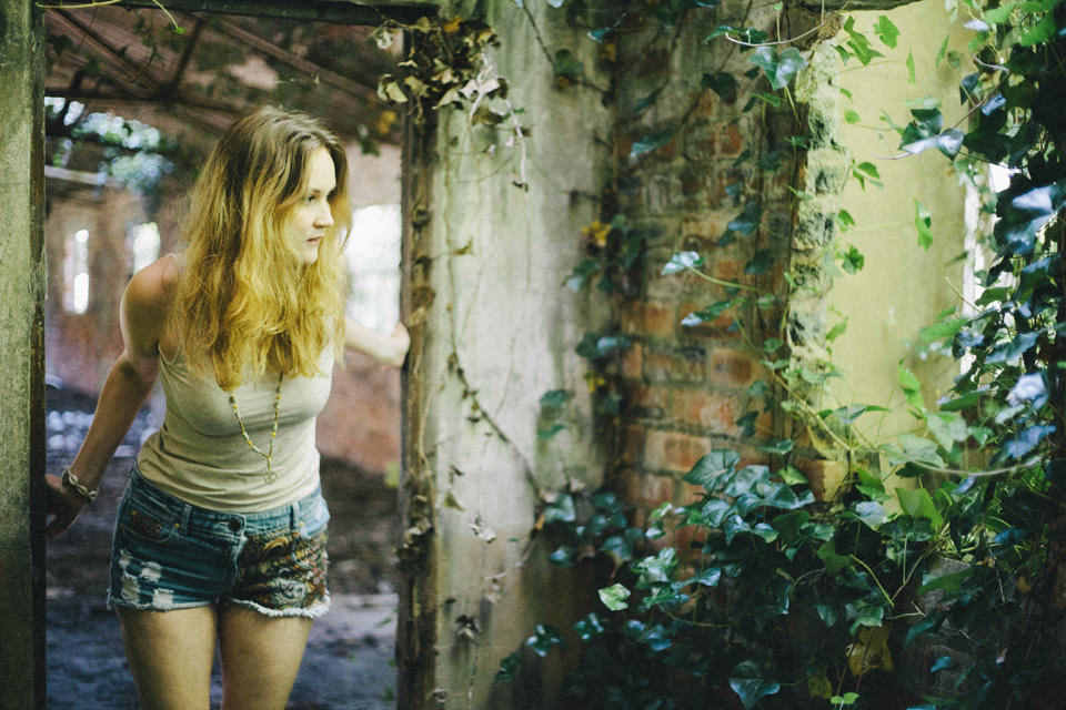 Model in abandoned building with light rays and overgrown ivy