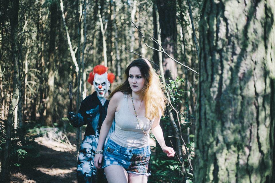 girl running away from killer clown in woods
