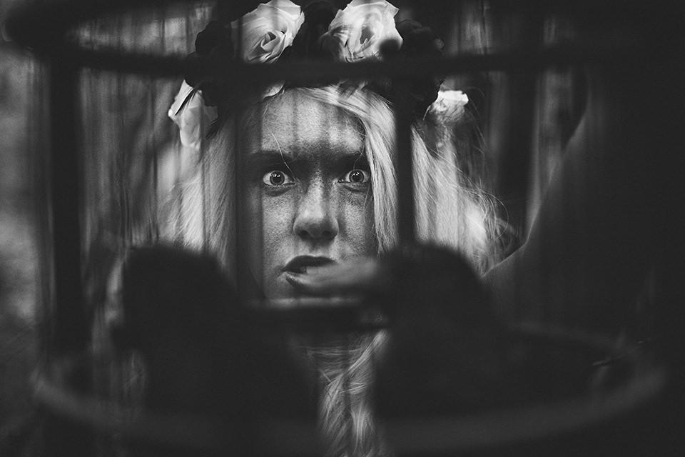 Womans face through a birdcage with crows