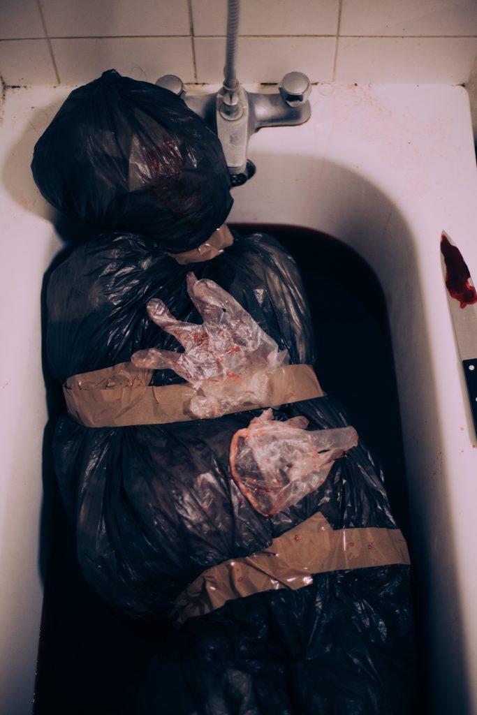 Dead body in a bag, in a bath tub full of blood