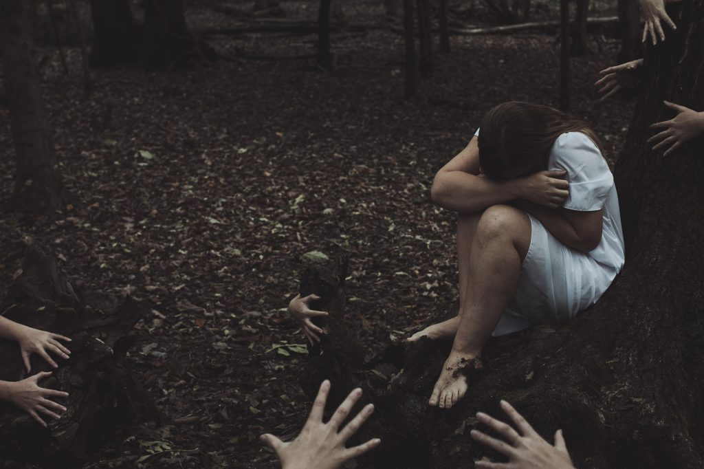 Creepy photograph of hands reaching towards woman in white in the woods