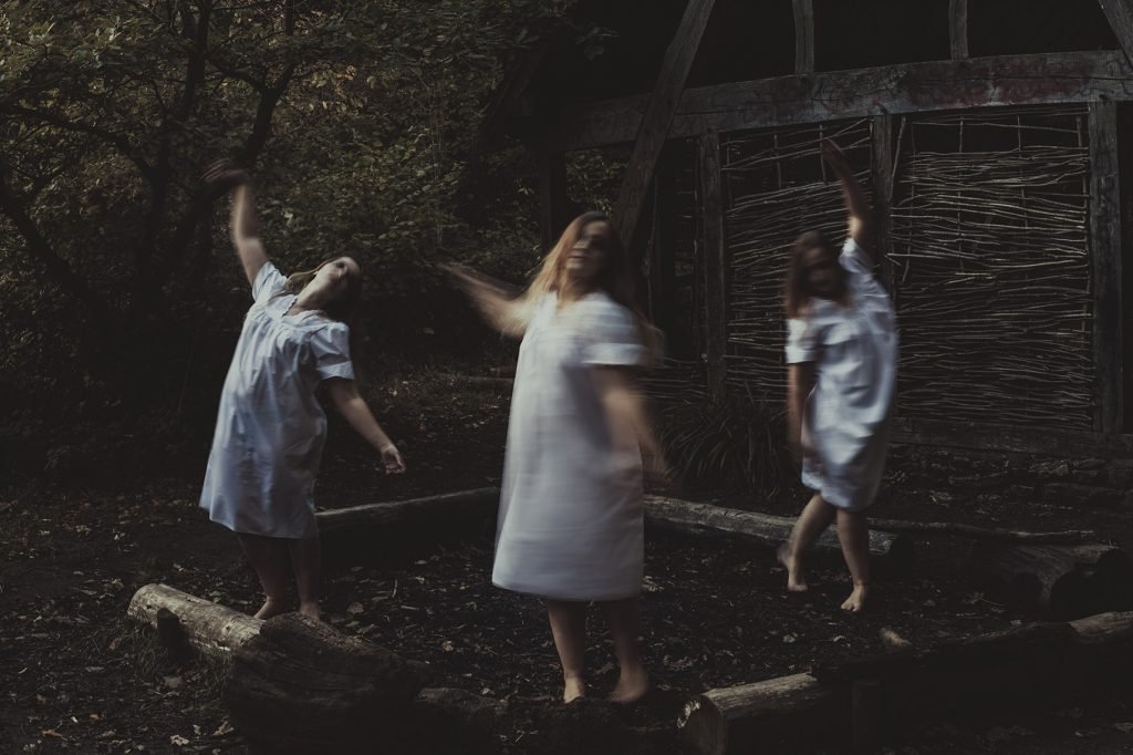 Occult Horror photograph of witches dancing around in front of a wooden house in the woods