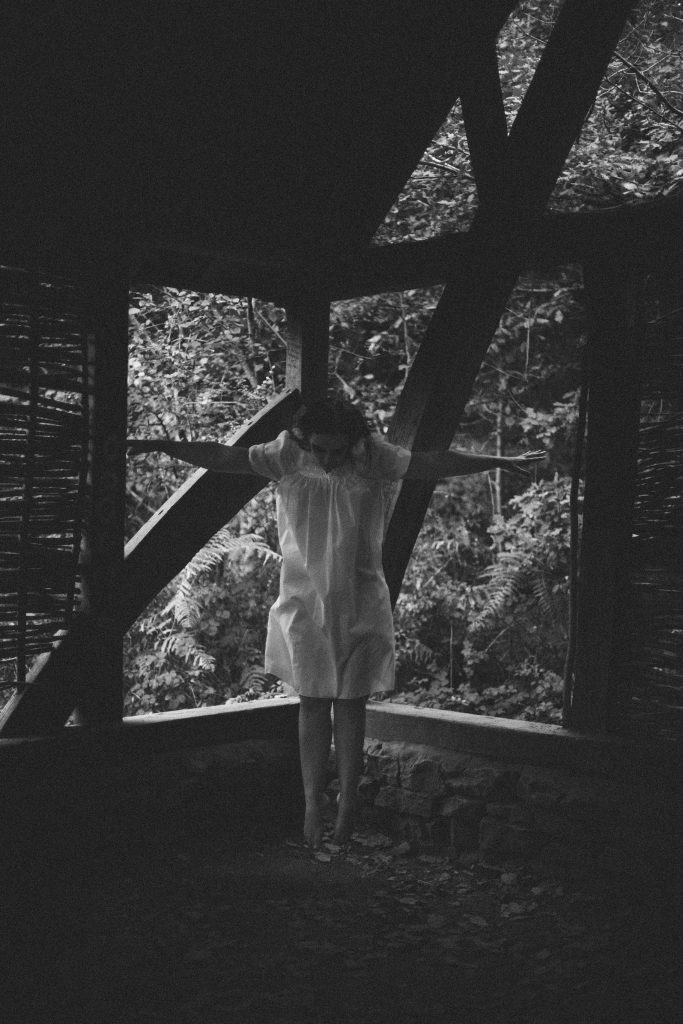 Black and white photography of woman in white dress levitating inside wooden house in the woods