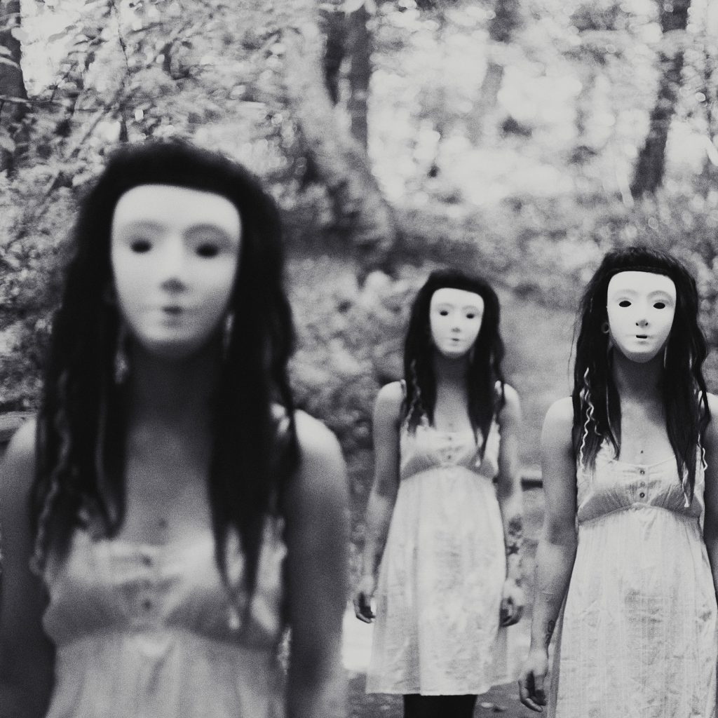 Black and white square format photograph of girls in masks, dressed in white with long black hair in the woods