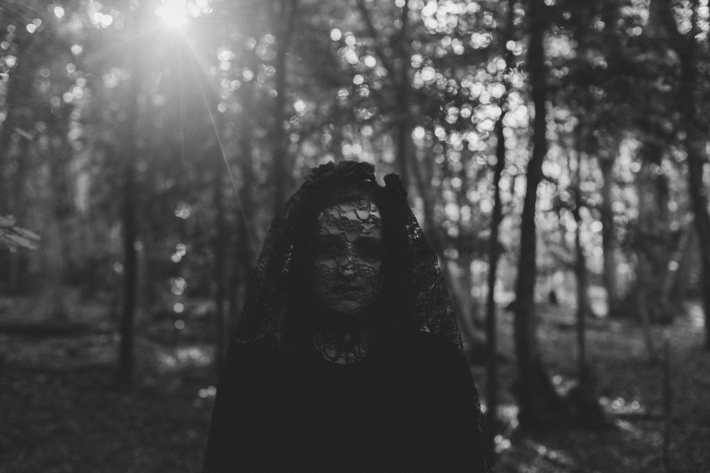 Woman in gothic black lace veil in the woods. Occult Horror Photography