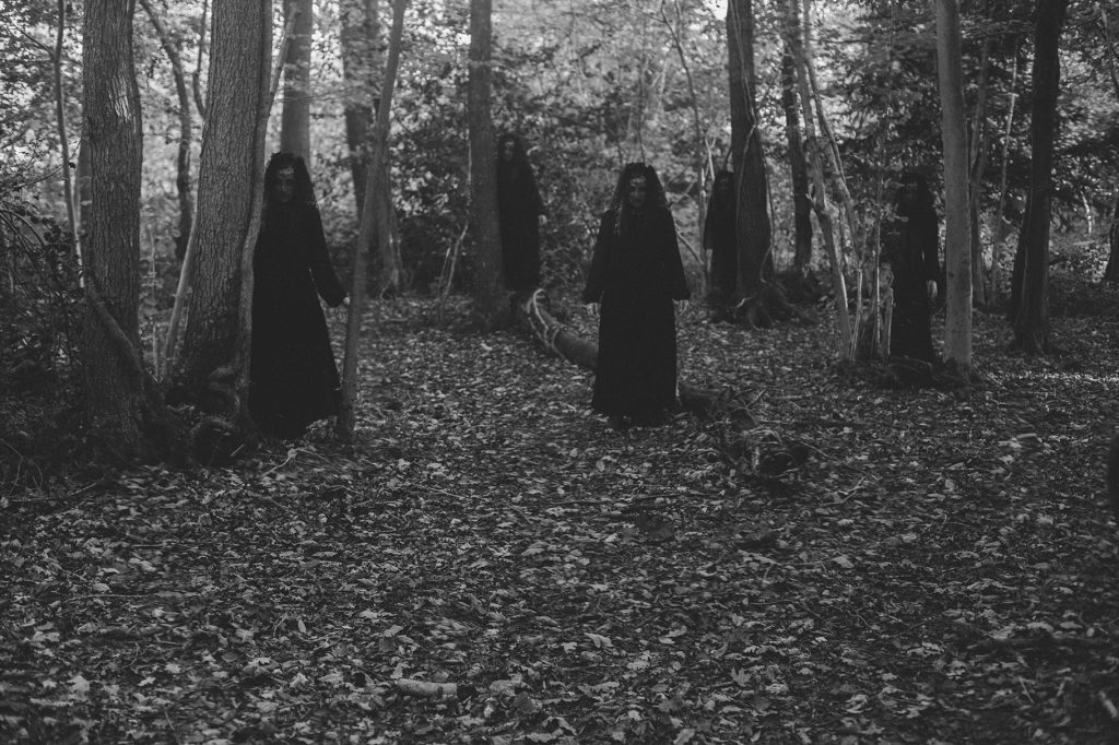 Creepy black and white photograph of witches in the woods wearing black veils and dresses