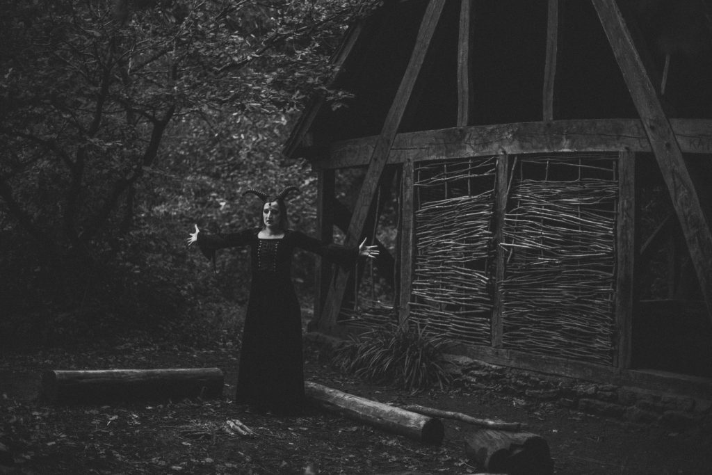 Black and white image of demon with horns and black gothic dress in front of wooden structure in the woods. Occult horror photography